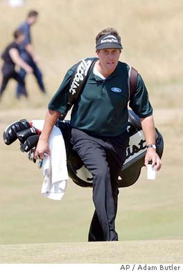 Phil of the United States carries his own clubs after sending his caddie to fetch a drink during a practice round for the upcoming British Open golf championship at Royal St. George's golf course in Sandwich, England, Monday, July 14, 2003. (AP Photo/Adam Butler) Photo: ADAM BUTLER