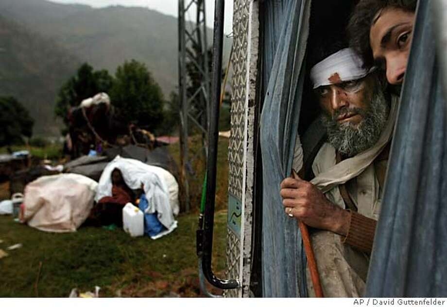 Pakistani earthquake survivors look out form the back of a truck as others take shelter from the rain on a road near Balakot, Pakistan, Tuesday, Oct. 11, 2005. (AP Photo/David Guttenfelder) Photo: DAVID GUTTENFELDER