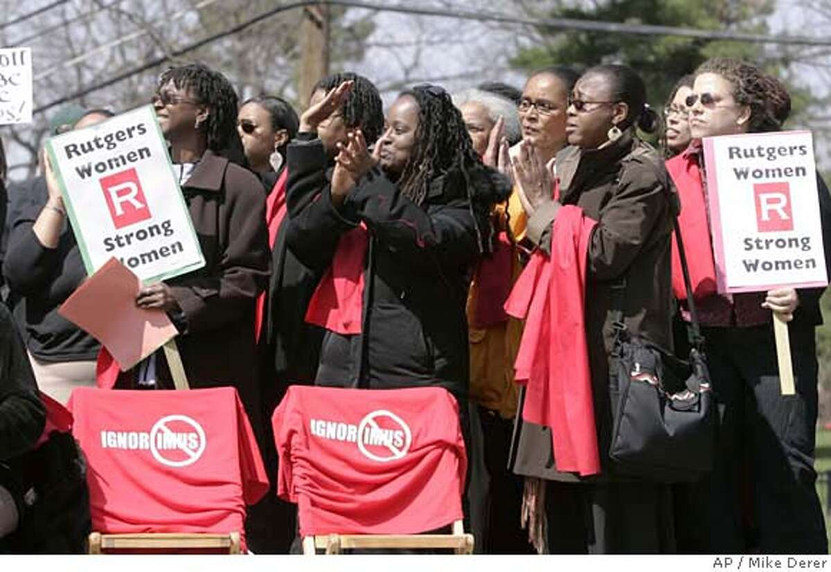 Female Rutgers University faculty members, including Kim D. Butler, wear red scarves during a rally on the Douglass College campus in New Brunswick, N.J., to protest comments radio talk show host Don Imus made about the Rutgers women's basketball team. (AP Photo/Mike Derer)