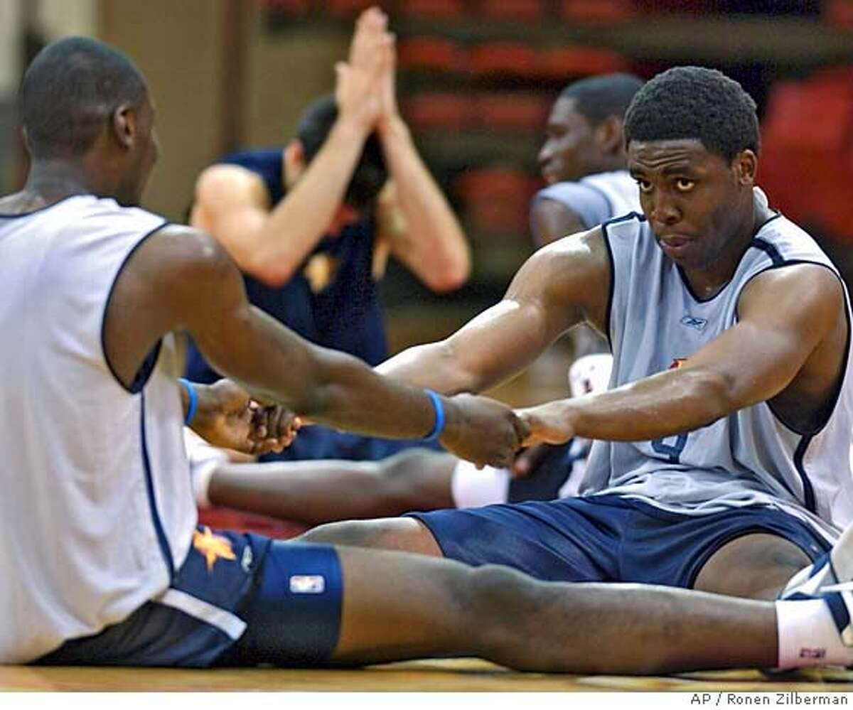 Golden State Warrior's Ike Diogu, right, stretches out with a fellow teammate, during a practice session in Laie, Hawaii, Thursday, Oct. 6, 2005. (AP Photo/Ronen Zilberman)