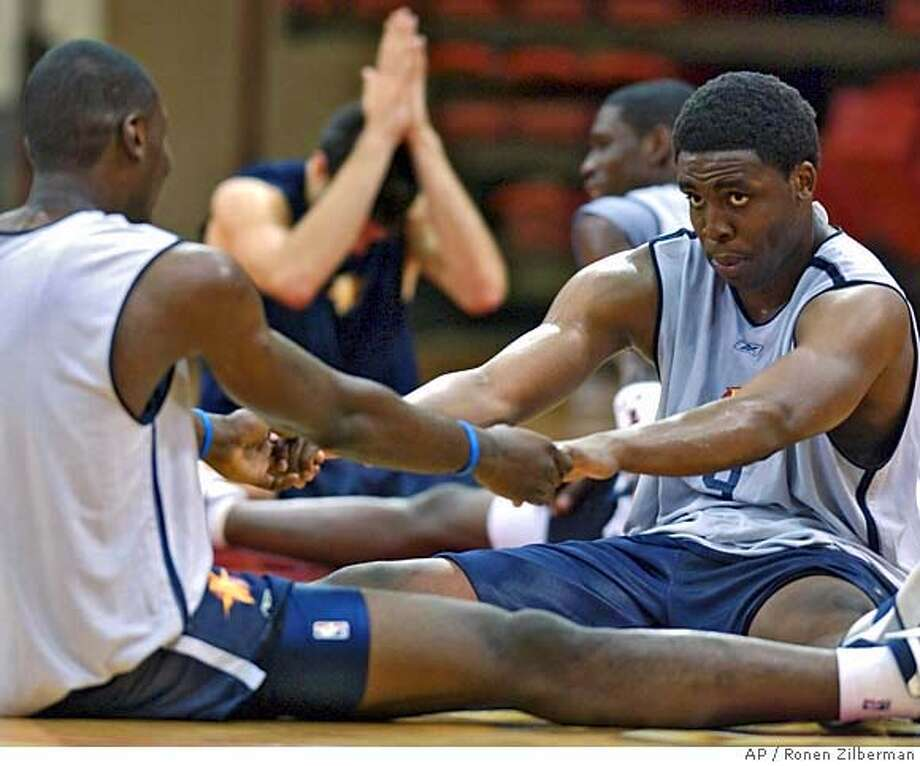 Golden State Warrior's Ike Diogu, right, stretches out with a fellow teammate, during a practice session in Laie, Hawaii, Thursday, Oct. 6, 2005. (AP Photo/Ronen Zilberman) Photo: RONEN ZILBERMAN