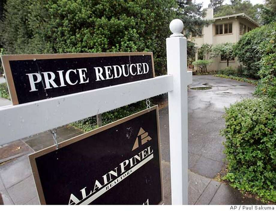 A Price Reduced sign is posted at a home for sale in Palo Alto, Calif., Wednesday, April 11, 2007. For the first time since at least The Beatles were still together, the median price for an existing home is expected to drop this year. The housing slump is in overdrive: On Capitol Hill, lawmakers warn local economies could be hurt by rising foreclosure rates. And a Boston-based nonprofit group says it has $1 billion from Citigroup and Bank of America to help refinance at-risk mortgages. (AP Photo/Paul Sakuma) Photo: Paul Sakuma