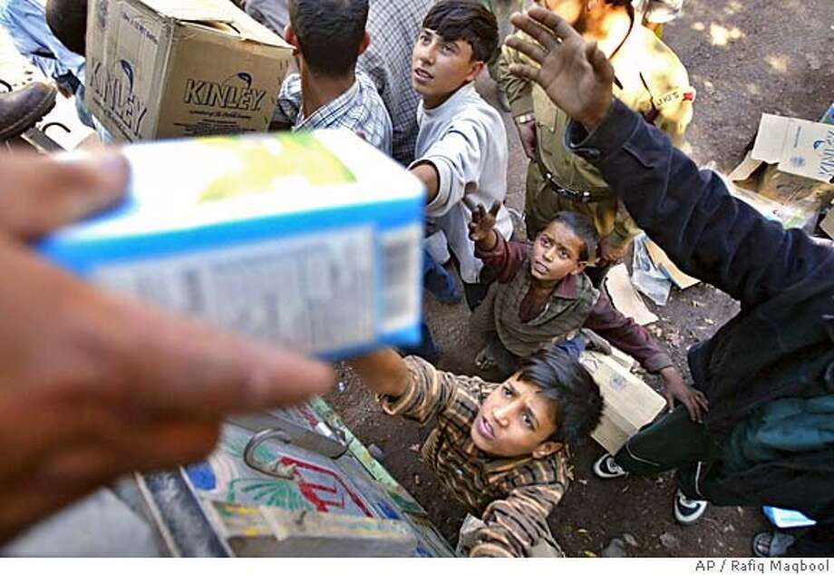 Volunteers distribute milk to earthquake victims at Jabla, near Uri, about 110 kilometers (69 miles) north of Srinagar, India, Sunday, Oct. 9, 2005. Soldiers and volunteers used bulldozers and bare hands Sunday to pull survivors and bodies from the rubble of houses and buildings toppled by a powerful earthquake in South Asia that killed 600 people in India's portion of the Kashmir region. (AP Photo/Rafiq Maqbool) Photo: RAFIQ MAQBOOL