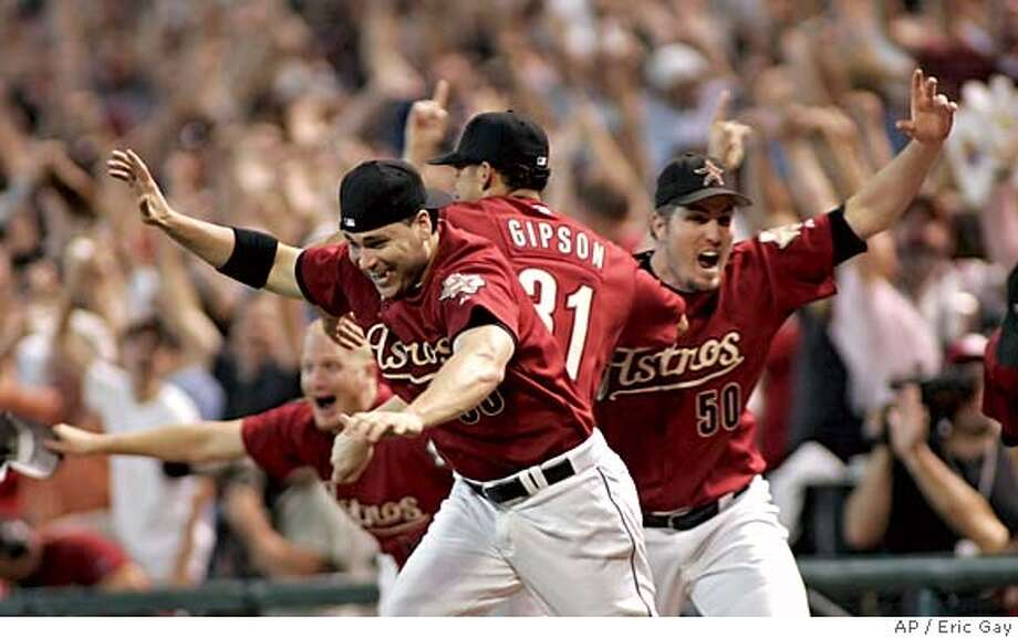 The Houston Astros celebrate defeating the Atlanta Braves 7-6 in the 18th inning of Game 4 of the National League Division Series Sunday, Oct. 9, 2005 in Houston. From right are Astros' Chad Qualls (50), Charles Gipson (31) Luke Scott and Mike Gallo. (AP Photo/Eric Gay) Photo: ERIC GAY