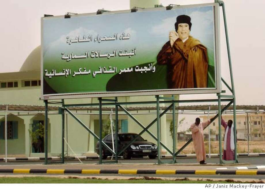 "A large billboard showing Libyan leader Moammar Gadhafi is seen on a street in his hometown of Sebha, Libya, Friday, March 30, 2007. The Arabic on the billboard reads ""From this pure desert blossomed the divine messages and brought Moammar Gadhafi the thinker of humanity."" (AP Photo/Janis Mackey-Frayer) ** CANADA OUT ** CANADA OUT PHOTO MADE AVAILABLE MONDAY APRIL 2 2007 Photo: JANIS MACKEY-FRAYER"