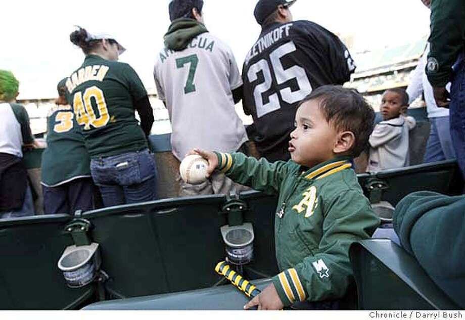 athletics_0001_db.JPG  Athletics' fan Desi Gutierrez, 1, with mother Marla Gutierrez of Stockton plays with a ball he recieved in pre-game at Oakland Athletics vs. Chicago White Sox home opener at McAfee Stadium in San Francisco, CA, on Monday, April, 9, 2007. photo taken: 4/9/07  Darryl Bush / The Chronicle ** Desi Gutierrez, Marla roster (cq) MANDATORY CREDIT FOR PHOTOG AND SF CHRONICLE/NO SALES-MAGS OUT Photo: Darryl Bush