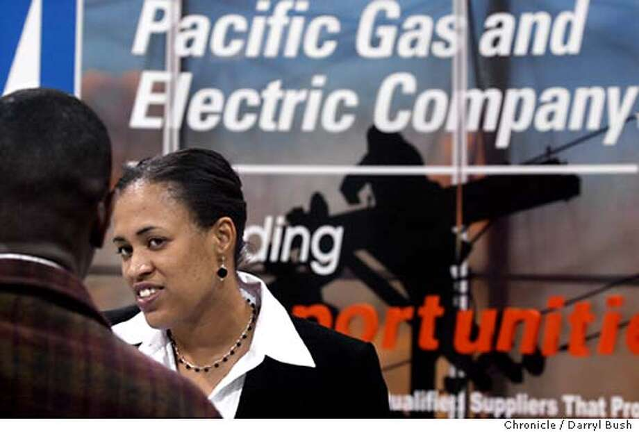 Jerilyn Gleaves, right, a Supplier Diversity Supervisor at PG&E Company in San Francisco, talks to those interesting in jobs at the PG&E booth at Black Expo 2003's Job Showcase and Procurement Fair at the Oakland Convention Center. 7/10/03 in Oakland.  DARRYL BUSH / The Chronicle Photo: DARRYL BUSH