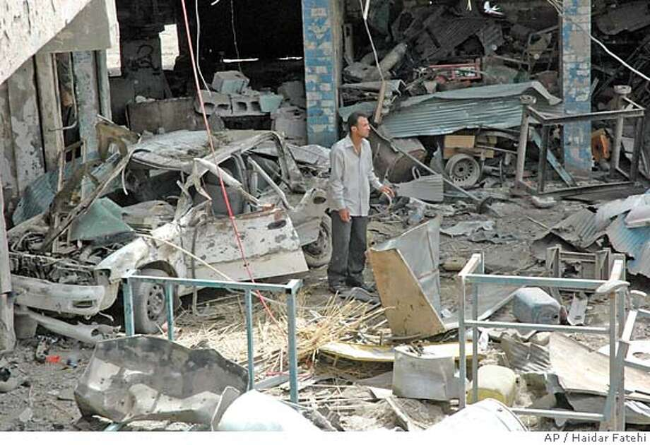 A man stands among the carnage after a pickup truck loaded with artillery shells exploded in the town of Mahmoudiyah, Iraq, 30 kilometers (20 miles) south of Baghdad, Sunday, April 8, 2007. At least 15 people were killed in the attack. (AP Photo/Haidar Fatehi) Photo: HAIDAR FATEHI