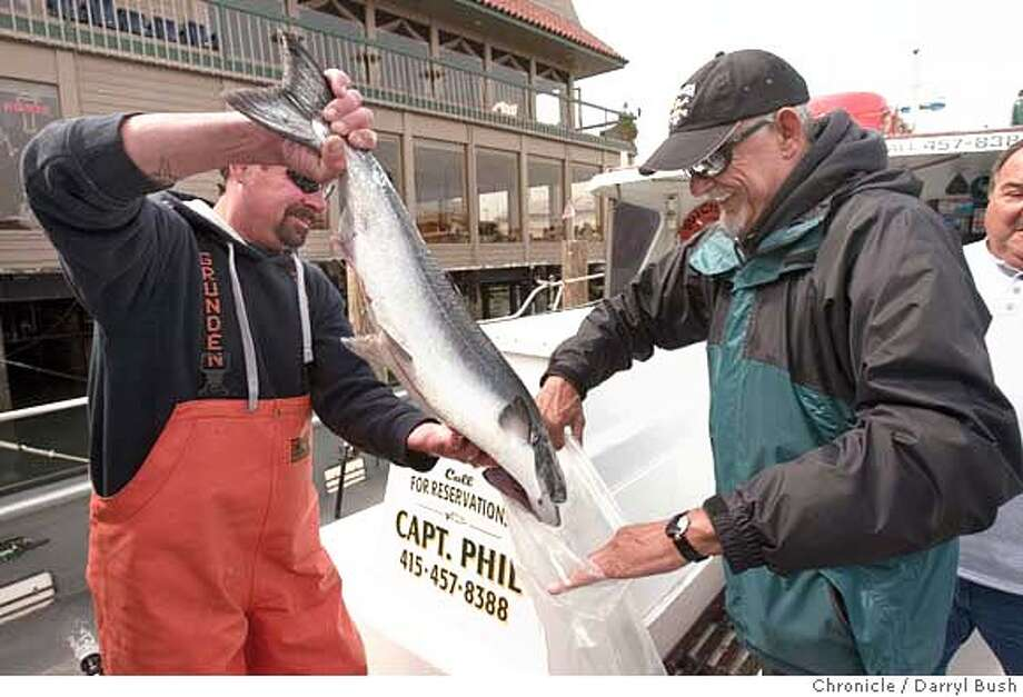 """Deck hand Jeff Claypool, left, helps angler Jim Copeland of Woodside (phone 650-851-8526) bag his 15 pound King salmon he caught (the largest caught on board of the day) aboard the sport fishing boat, """"Butchie B"""" as Copeland prepares to take it home on the first day of salmon season at Fisherman's Wharf in San Francisco, CA, on Saturday, April, 7, 2007. Only 8 salmon were caught near Point Montara. photo taken: 4/7/07  Darryl Bush / The Chronicle ** Jim Copeland, Jeff Claypool (cq) Photo: Darryl Bush"""