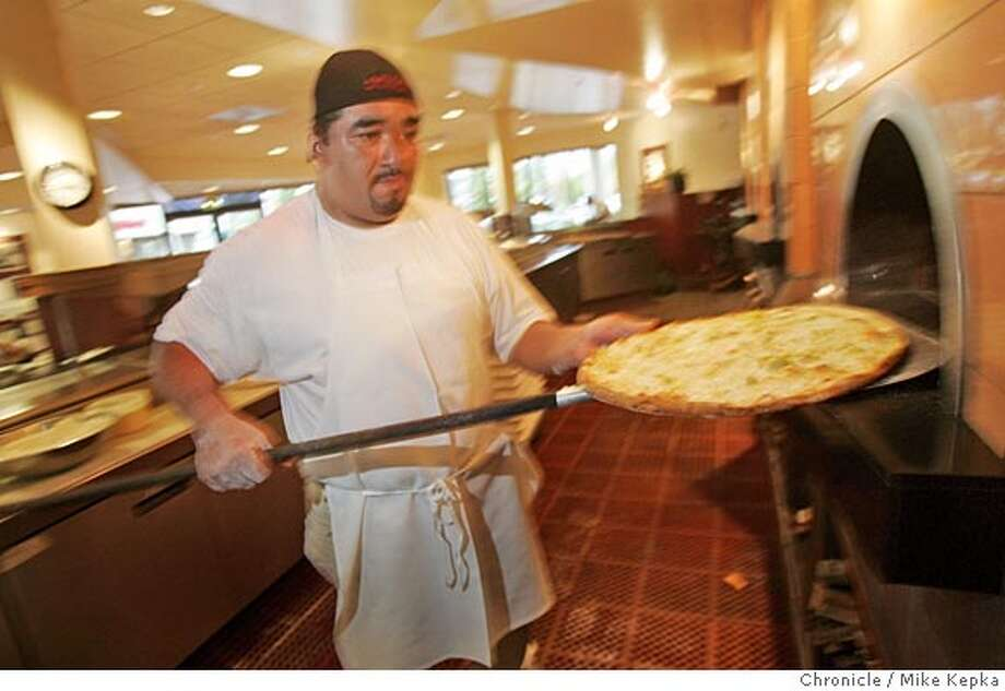 pnamici30136_mk.JPG Mario Dominguez checks an order at Amici's East Coast Pizzeria in San Carlos 9/20/05 Mike Kepka / The Chronicle Ran on: 09-30-2005  Peter Cooperstein, left, founded Amici's so he could eat East Coast-style pizza like the one Mario Dominguez, right, is turning out. MANDATORY CREDIT FOR PHOTOG AND SF CHRONICLE/ -MAGS OUT Photo: Mike Kepka