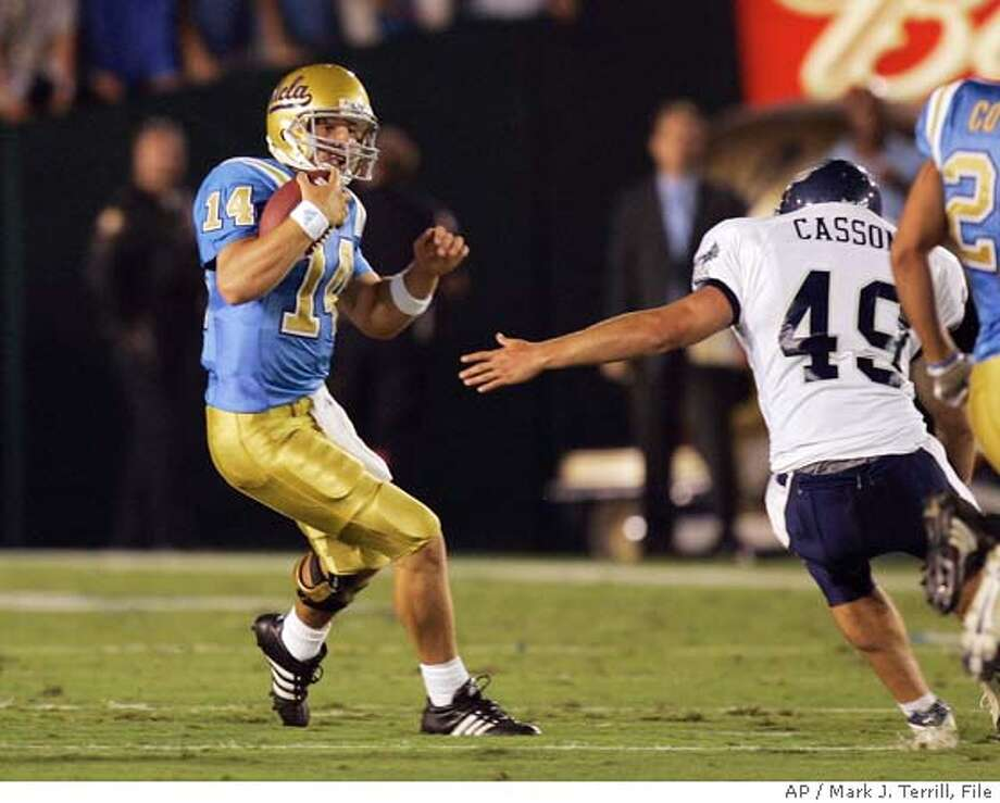 UCLA quarterback Drew Olson runs the ball as he avoids a tackle by Rice's Buck Casson, right, during the first half, Saturday, Sept. 10, 2005, in Pasadena, Calif. UCLA takes on No. 21 Oklahoma on Saturday, Sept. 17, 2005, in Los Angeles. (AP Photo/Mark J. Terrill) Photo: MARK J. TERRILL