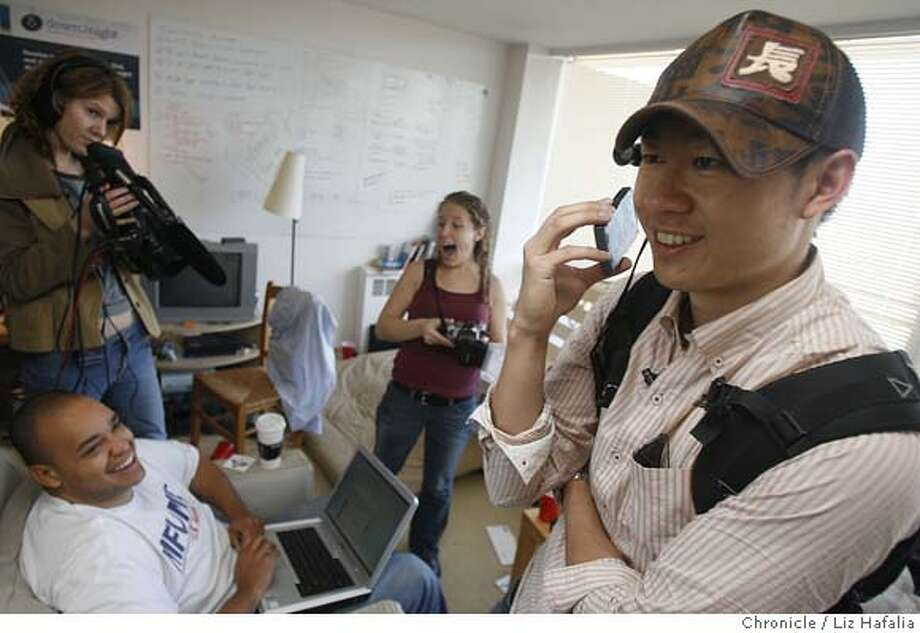 JUSTINTV_097_LH_.jpg Justin Kan wears a camera that's on 24/7 that folks follow along on the Web. He is on the telephone doing an interview with NBC's Los Angeles affiliate while looking at himself in a mirror at 10:57am. Beside him is Michael Seibel (left), SF Gate photographer, and Lindsay Docherty (middle) .  Liz Hafalia/The Chronicle/San Francisco/3/29/07  ** Justin Kan, Lindsay Docherty, cq �2007, San Francisco Chronicle/ Liz Hafalia  MANDATORY CREDIT FOR PHOTOG AND SAN FRANCISCO CHRONICLE. NO SALES- MAGS OUT. Photo: Liz Hafalia