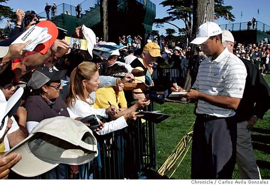 Tiger Woods signs autographs for fans after finishing a practice round on the back nine at Harding Park Golf Course in San Francisco, Ca., on October 4, 2005. First day of practice on Tuesday, October 4, 2005, for the American Express Championship at Harding Park Golf Course in San Francisco, Ca. Photo by Carlos Avila Gonzalez / The San Francisco Chronicle  Photo taken on 10/4/05, in San Francisco,CA. Photo: Carlos Avila Gonzalez