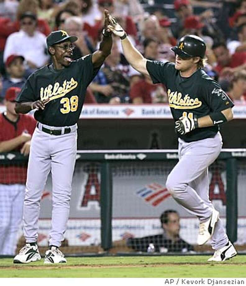 Oakland Atheltics' third base coach Ron Washington congratulates Dan Johnson after he hit a solo home run off Los Angeles Angels pitcher Jarrod Washburn during the seventh inning of the game Tuesday, July 19, 2005, in Anaheim, Calif. (AP Photo/Kevork Djansezian) Ran on: 07-20-2005  Rich Harden wasn't perfect, but he was more than good enough as he took a shutout into the ninth inning in Anaheim. Ran on: 07-20-2005  Rich Harden wasn't perfect, but he was more than good enough as he took a shutout into the ninth inning in Anaheim. Photo: KEVORK DJANSEZIAN