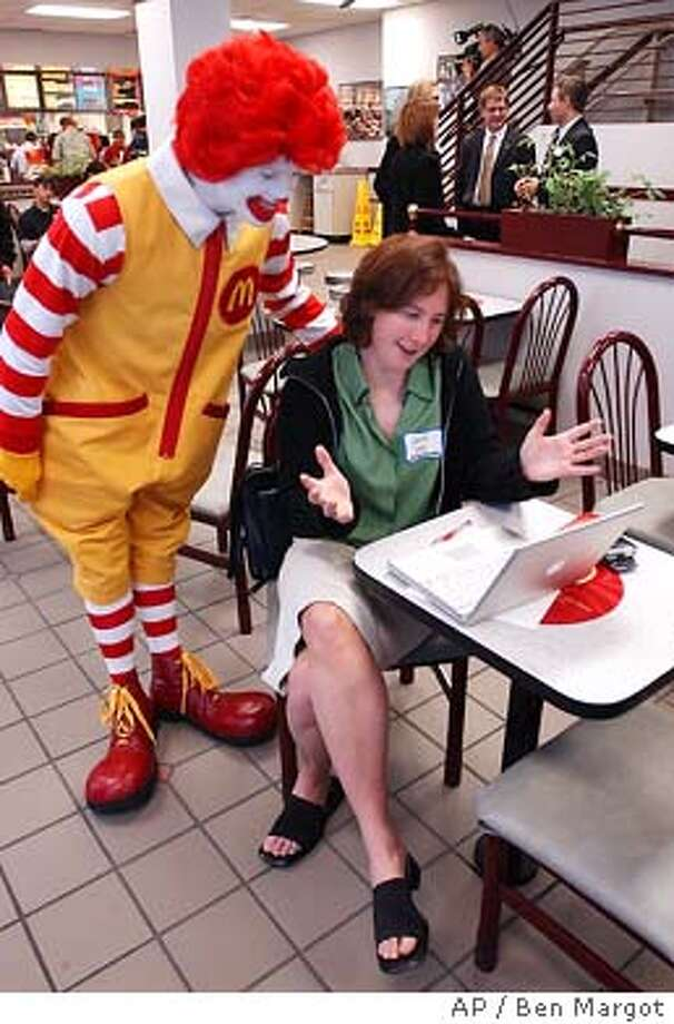 Julie Ask, a senior analyst for Jupiter Research of San Francisco, connects her laptop to a wireless internet connection while being supervised by Ronald McDonald Tuesday, July 8, 2003, at a McDonald's restaurant in the financial district of San Francisco. Selected McDonalds' restaurants in the San Francisco Bay Area will offer high speed wireless internet connectivity for $4.95 per 2 hour usage. (Photo/Ben Margot) Photo: BEN MARGOT