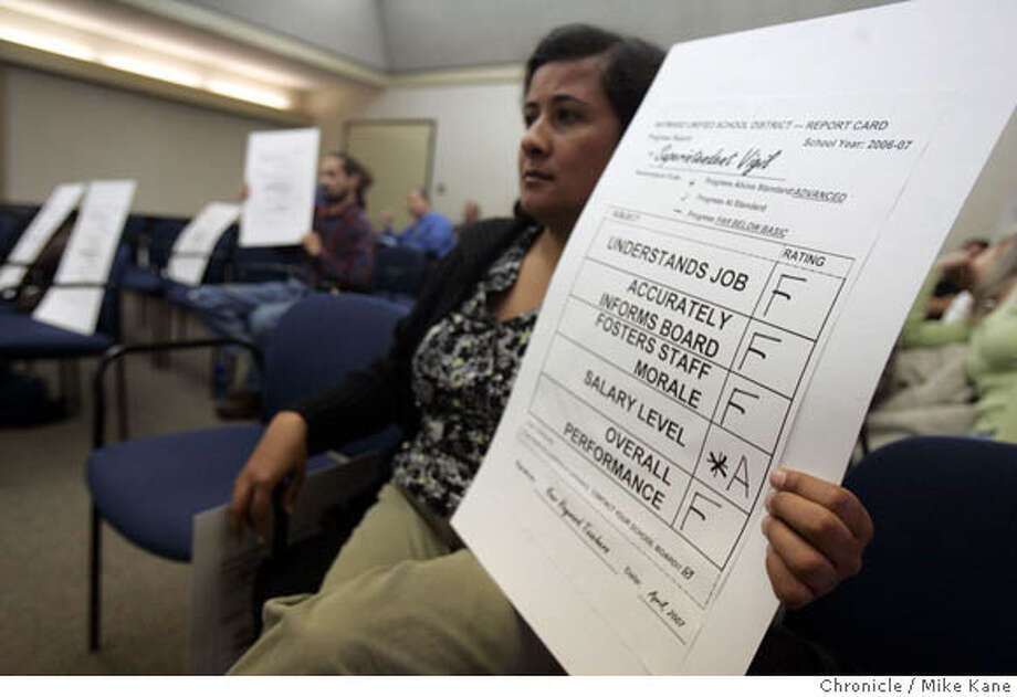 Park Elementary kindergarten teacher Carmela Carlos holds a mock report card expressing union assessment of Hayward Unified School Superintendent Dale Vigil at a school board meeting on the eve of a threatened strike over wages in Hayward, CA, on Wednesday, April, 4, 2007. photo taken: 4/4/07  Mike Kane / The Chronicle ** Carmela Carlos Photo: MIKE KANE