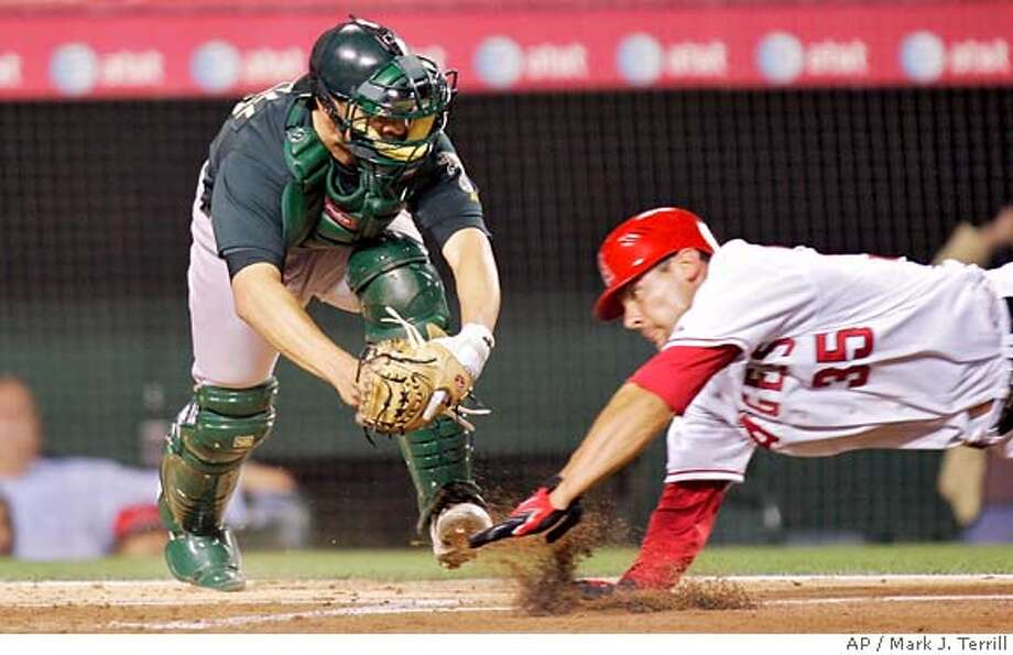 Oakland Athletics catcher Jason Kendall gets set to tag out Los Angeles Angels' Casey Kotchman, who was trying to score from second on a hit by the Angels' Maicer Izturis during the second inning of their baseball game, Thursday, April 5, 2007, in Anaheim, Calif. (AP Photo/Mark J. Terrill) Photo: Mark J. Terrill