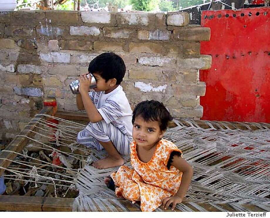 slum2.jpg For Mark Abel ; Children sit on a makeshift tea bed in the France Colony slum in Islamabad. The area, which took its' name from its proximity to the French Embassy here, is home to over 800 families. Photo credit: Juliette Terzieff ; on 7/1/03 in . Juliette Terzieff / HO Photo: Juliette Terzieff