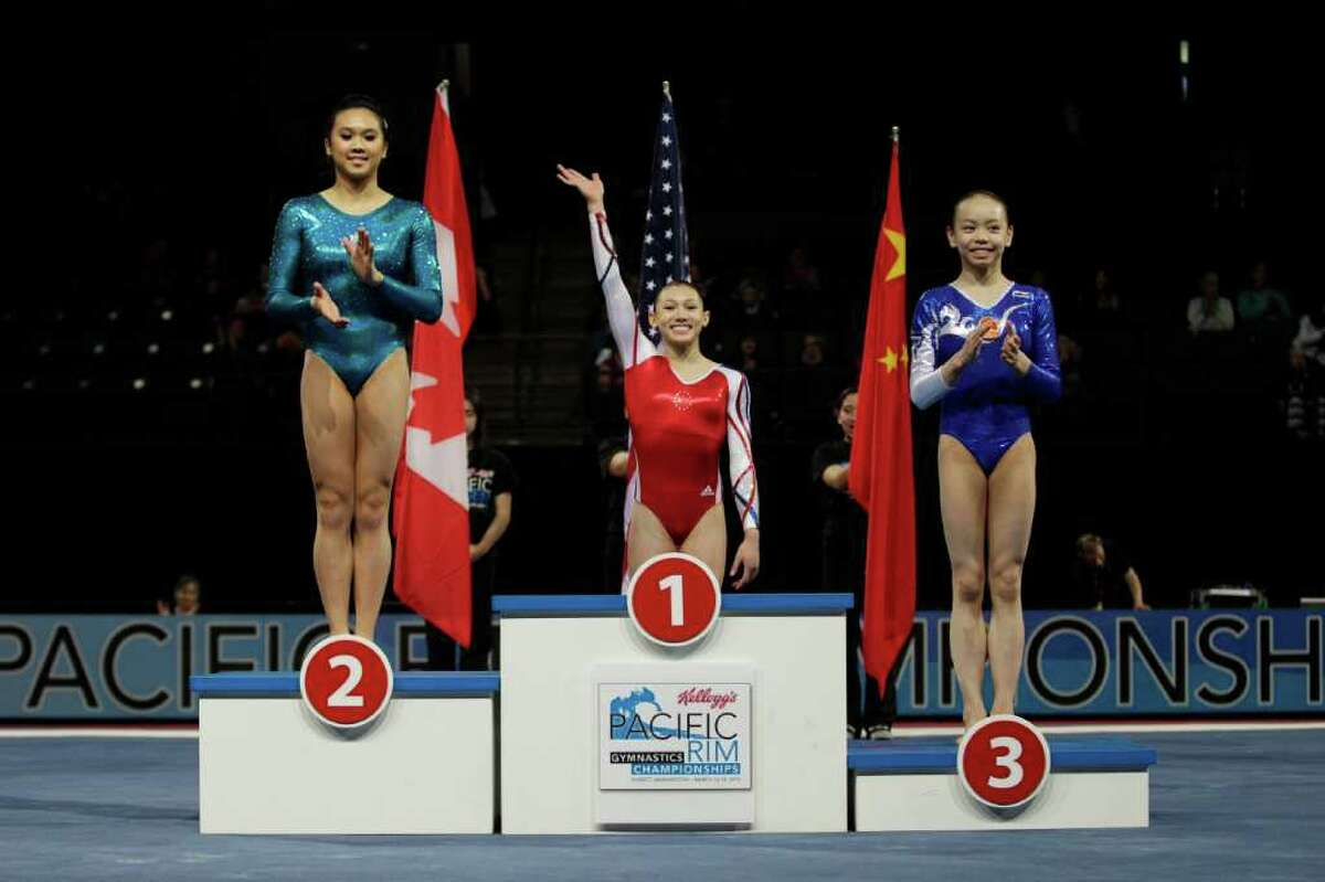 Kyla Ross, center, of the United States, celebrates her gold medal in the balance beam as silver medal winner Christine Lee, left, of Canada, and bronze medalist Tan Sixin, right, of China, join her on the podium, Sunday, March 18, 2012, in the senior individual championships of the Pacific Rim Gymnastics Championships in Everett, Wash.