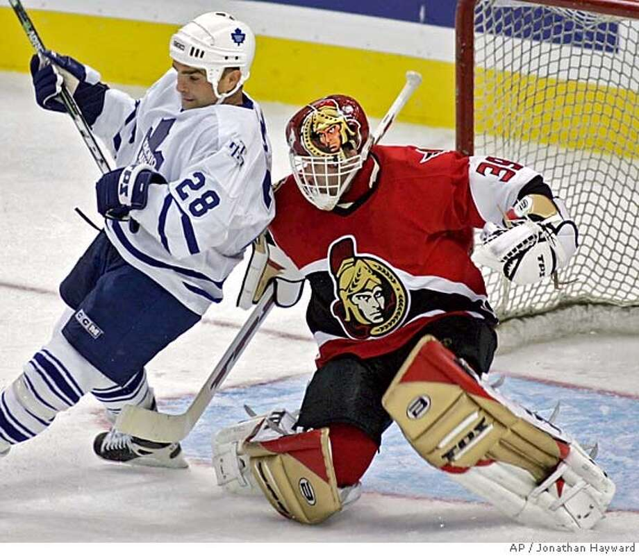 Ottawa Senators goaltender Dominik Hasek, right, tries to clear Toronto Maple Leafs Tie Domi from in front of the net during first period NHL preseason action at the Corel Centre in Ottawa Sunday, Sept. 25, 2005.(AP PHOTO/CP, Jonathan Hayward) Photo: JONATHAN HAYWARD