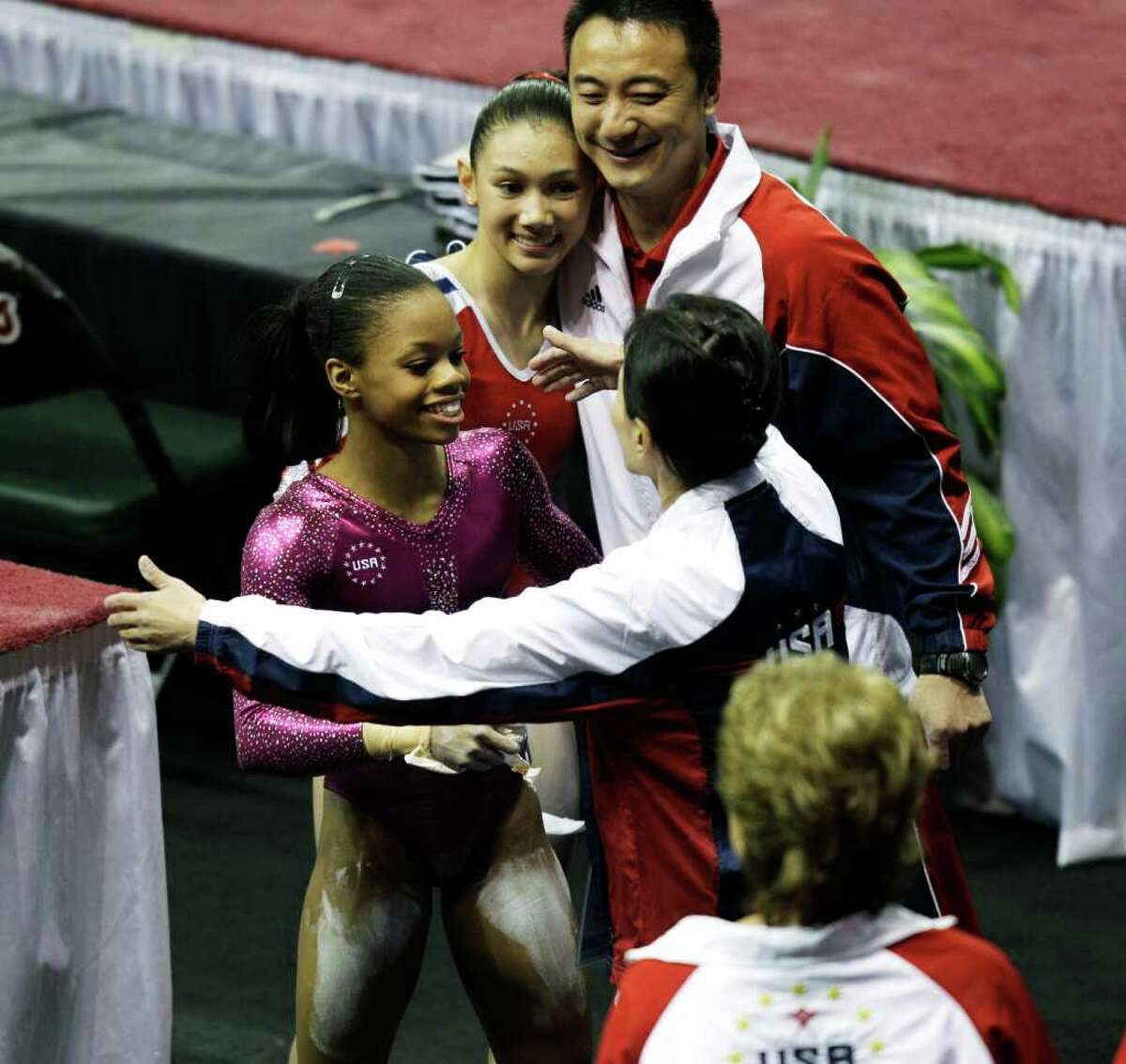 United States gymnasts Gabrielle Douglas, left, and Kyla Ross, second from left, hug their coaches after Douglas took first and Ross took second in the uneven bars, Sunday, March 18, 2012, in the Pacific Rim Gymnastics Championships in Everett, Wash.