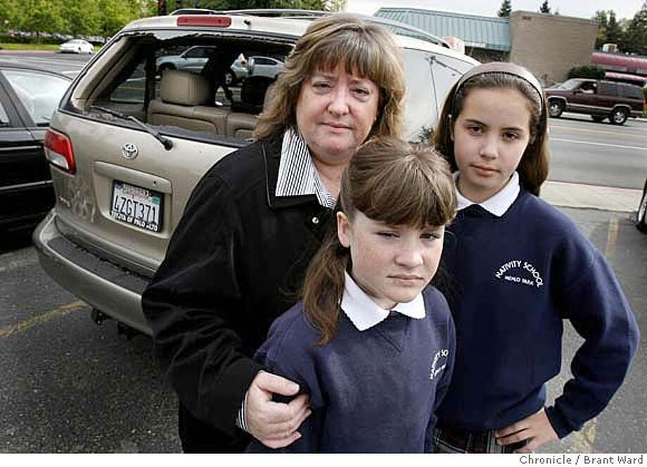 criticalmass027.JPG  L-R Mother Susan Ferrando, daughter Shannon and daughter Lauren, 13, next to their van which had the back window broken.  Susan Ferrando and her two daughters were in San Francisco to celebrate daughter Shannon's 11th birthday when they were attacked by members of the monthly Critical Mass bicycle ride. They are photographed at a Peninsula autobody shop where work is being done on their van.  {Brant Ward/San Francisco Chronicle}4/4/07 Photo: Brant Ward