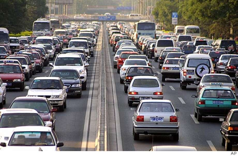 ** ADVANCE FOR SUNDAY, MAY 29 **FILE**Cars clog Beijing's Second Ring Road in the afternoon rush hour Thursday, June 10, 2004. Car sales in China are expected to total as many as 10 million vehicles annually by 2010. In Beijing alone, more than 1000 new cars hit the city's streets each day, resulting in major traffic problems and much higher energy use. (AP Photo/str) Ran on: 05-29-2005  About 8 percent of Canada's oil is produced by liquefying oil found in tar sands. Workers here overlook Suncor's tar sands processing plant in Fort McMurray, Alberta. Ran on: 07-06-2005  A woman rides her bicycle past a poster for new cars in Beijing. Ran on: 07-06-2005  A woman rides her bicycle past a poster for new cars in Beijing. Ran on: 07-06-2005  A woman rides her bicycle past a poster for new cars in Beijing. HFR 05-29-05. ADVANCE FOR SUNDAY, MAY 29 Photo: Ap