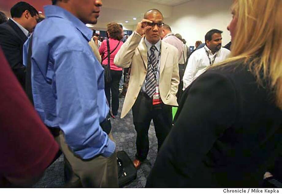 """Calling himself """"The modern business Man,"""" Kenton Ho of Ontario Canada waits in line to hear Larry Ellison give his keynote speech at Oracle OpenWorld.  on location Oracle Open World 9/21/05 Mike Kepka / The Chronicle Photo: Mike Kepka"""