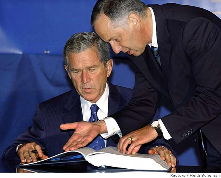 U.S. President George W. Bush (L) prepares to sign the International Convention for the Suppression of Acts of Nuclear Terrorism Treaty as Nicholas Michel watches at the United Nations in New York September 14, 2005. Bush told a U.N summit on Wednesday that the U.S. was prepared to drop all trade tariffs, subsidies and other barriers if other nations did the same. REUTERS/Heidi Schuman 0 Photo: HEIDI SCHUMANN