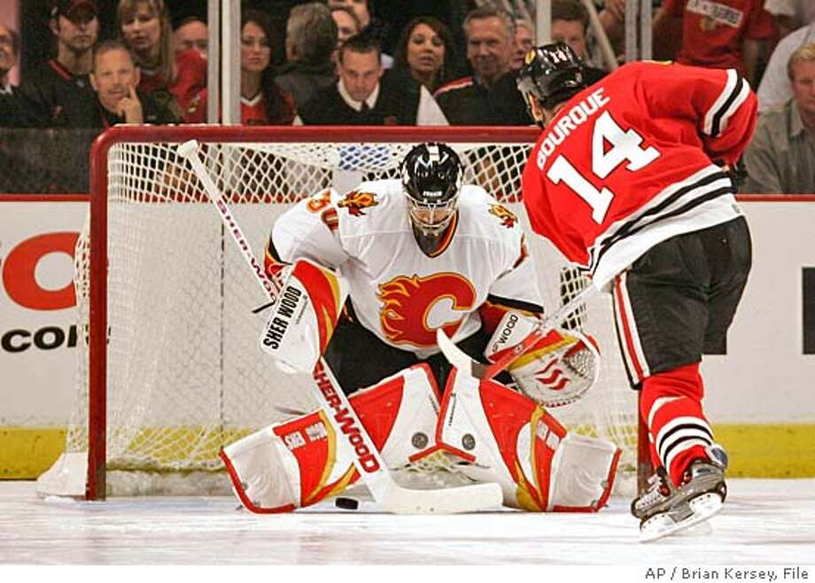 Chicago Blackhawks' Rene Bourque (14) scores on Calgary Flames' goaltender Philippe Sauve (30) during a demonstration of the shootout senario after the game, Saturday, Sept. 17, 2005, in Chicago. The Blackhawks won, 5-4, in regualtion, but the teams had a shootout for the fans to demonstrate the new rule calling for a shootout after a five-minute, sudden-death overtime period. (AP Photo/Brian Kersey) Photo: BRIAN KERSEY