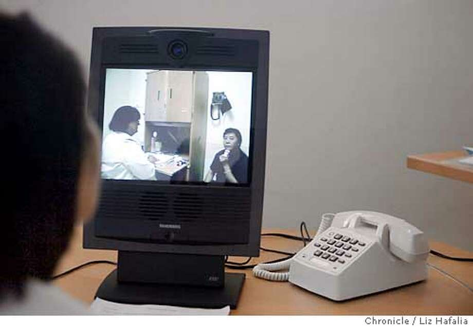 Highland Hospital in Oakland is testing a new video translation system--where medical translators can be accessed through computer and phone through one location (rather than running around)--designed to be used in other hospitals. Patient Shing Saeturn asking the translator about medication she's taking for hypertension. Doctor Linda Engelstad on left of screen. Medical translator Nai F. Saeteurn in foreground shadow. Shot on 7/1/03 in Oakland. LIZ HAFALIA / The Chronicle Photo: LIZ HAFALIA