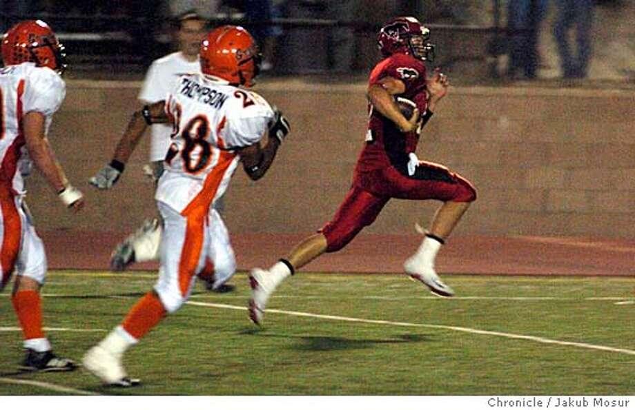 Monte Vista QB Drew McCallister rushes for a touchdown against California's Brandon Thompson. / Jakub Mosur / The Chronicle