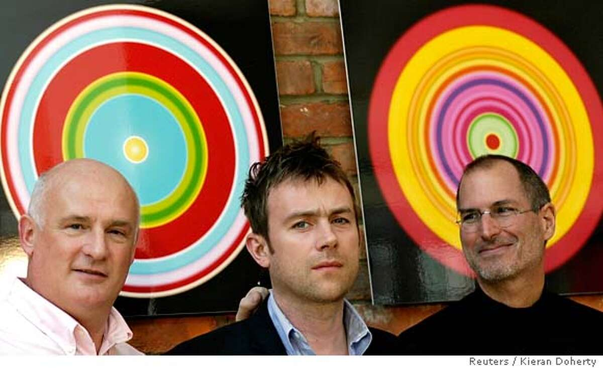 Chief Executive Officer (CEO) of EMI Group Eric Nicoli (L) and CEO of Apple Steve Jobs pose for photographers with British musician Damon Albarn (C) in London April 2, 2007. EMI Group Plc said on Monday it was making its music catalogue available through Apple Inc's iTunes store without the anti-piracy measure known as digital rights management (DRM). REUTERS/Kieran Doherty (BRITAIN)