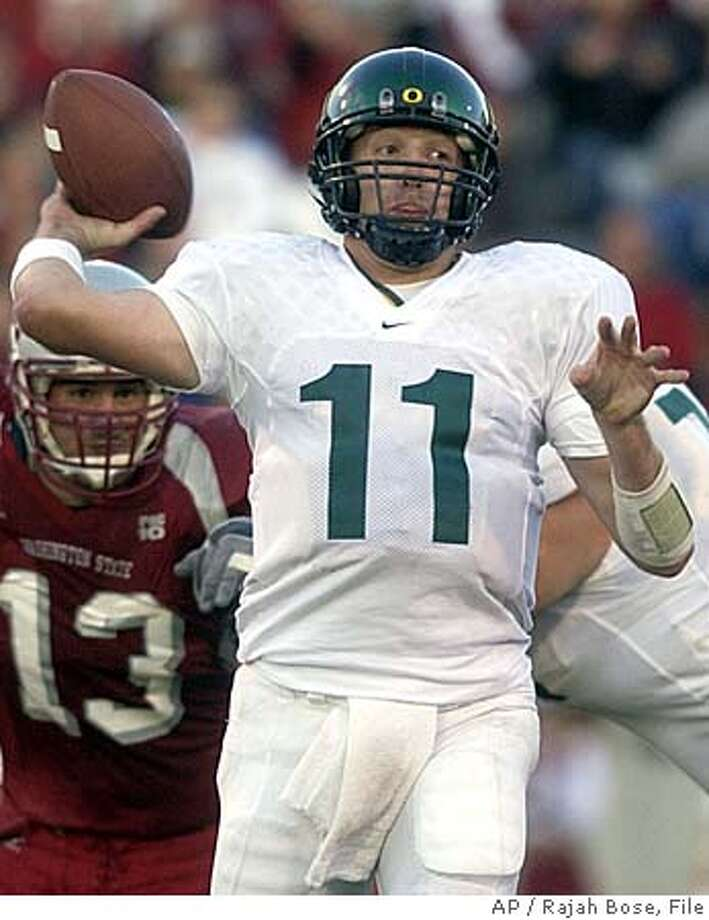 **FILE** Oregon's Kellen Clemens throws as Washington's Adam Braidwood moves in from behind during the third quarter in Pullman Saturday October, 9, 2004. Clemens will face Matt Leinart and Southern California this weekend. Leinart and Clemens are both difference-making quarterbacks for their teams, and they're meeting Saturday on the field for the first time.(AP Photo/Rajah Bose, File) OCTOBER, 9, 2004 FILE PHOTO Photo: RAJAH BOSE