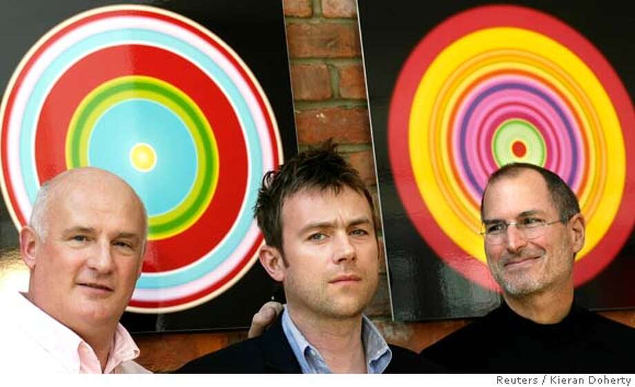 Chief Executive Officer (CEO) of EMI Group Eric Nicoli (L) and CEO of Apple Steve Jobs pose for photographers with British musician Damon Albarn (C) in London April 2, 2007. EMI Group Plc said on Monday it was making its music catalogue available through Apple Inc's iTunes store without the anti-piracy measure known as digital rights management (DRM). REUTERS/Kieran Doherty (BRITAIN) Photo: KIERAN DOHERTY