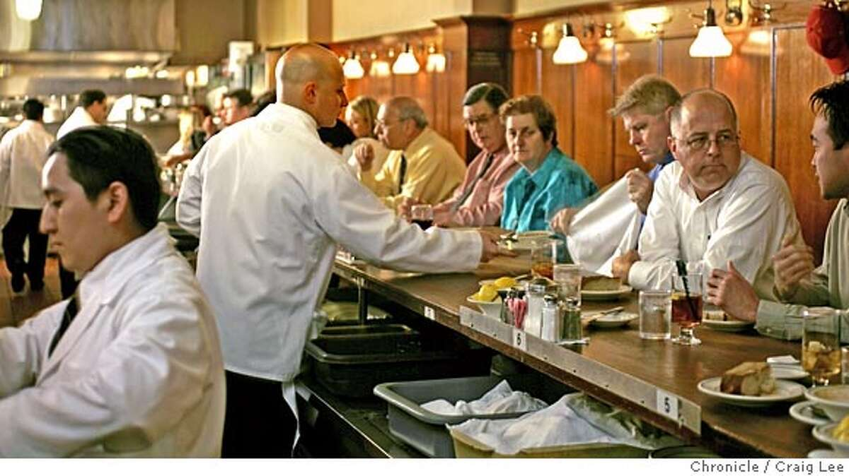 Story on Tadich Grill, 240 California Street. Waiter Barry Schwartz, serving at the bar during lunch. Busboy, Gabriel Lopez, at the far left. Event on 8/23/05 in San Francisco. Craig Lee / The Chronicle