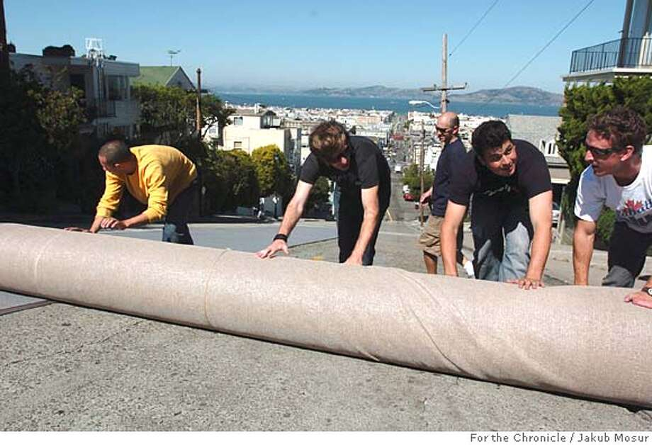 Workers roll out a carpet to be used by Icer Air 2005, a promotional ski-jump contest on San Francisco's Fillmore Street in Pacific Heights.  Event on 9/28/05 in San Francisco. JAKUB MOSUR / The Chronicle Photo: JAKUB MOSUR