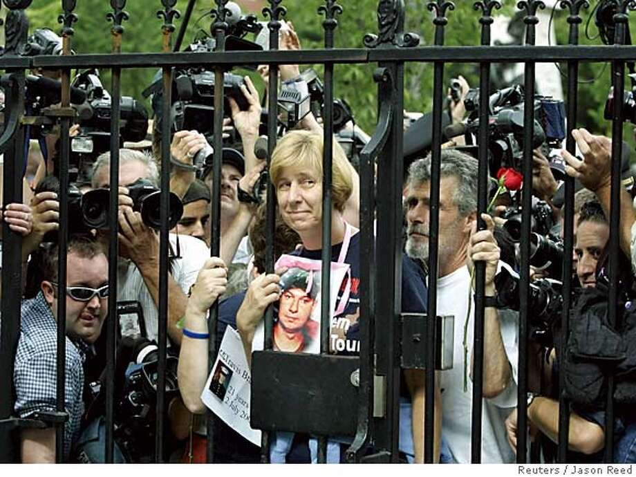 Anti-war protester Cindy Sheehan (C) of Vacaville, CA, holds a portrait of her dead military son Casey, as she stands at the gates of the White House in Washington to ask for a meeting with U.S. President George W. Bush September 26, 2005. U.S. military mother Cindy Sheehan, whose vigil outside Bush's Texas ranch focused attention on the anti-war movement, was arrested on Monday in a sit-in at the White House after refusing to obey police orders to leave. REUTERS/Jason Reed 0 Photo: JASON REED