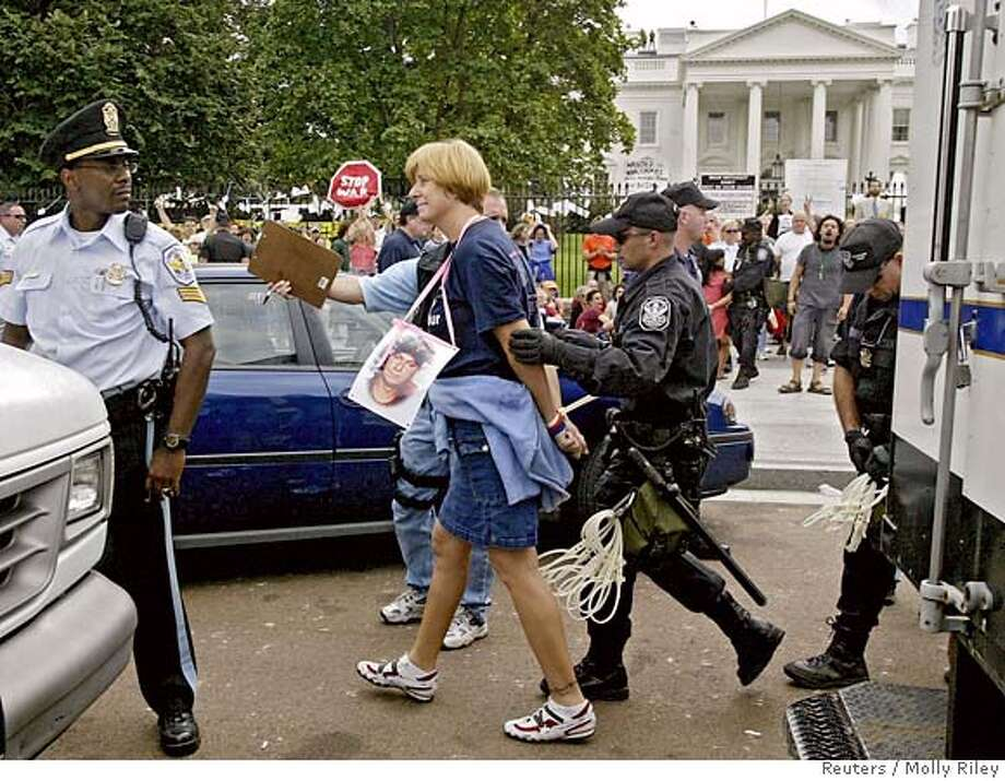 Anti-war protester and mother of a son who was killed in Iraq Cindy Sheehan (C) is arrested in front of the White House by U.S. Park Police during a protest in Washington September 26, 2005. Sheehan, whose vigil outside President George W. Bush's Texas ranch focused attention on the anti-war movement, was arrested on Monday in a sit-in at the White House after refusing to obey police orders to leave. REUTERS/Molly Riley Photo: MOLLY RILEY