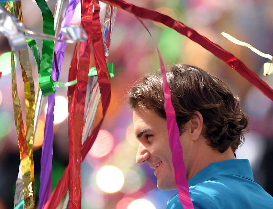INDIAN WELLS, CA - MARCH 18:  Roger Federer of Switzerland smiles as streamers fall after a 7-6(7), 6-3 win over John Isner during the ATP Singles Final at the Indian Wells Tennis Garden on March 18, 2012 in Indian Wells, California.  (Photo by Harry How/Getty Images) Photo: Harry How, Getty Images