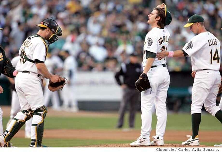 Kirk Saarloos gets a pat on the back as he is relieved in the fourth inning. The Oakland Athletics played the Texas Rangers at McAfee Coliseum in Oakland, Ca., on Sunday, September 25, 2005. The A's watched they playoff hopes dwindle as they lost 6-2 against the Rangers, remaining 4 games back of their American League West division rivals the LA Angels. Photo by Carlos Avila Gonzalez / The San Francisco Chronicle  Photo taken on 9/25/05, in Oakland,CA. Photo: Carlos Avila Gonzalez