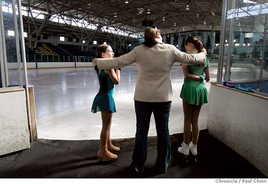 Skating coach Kara Tiedemann (center) offers last-minute encouragement for Elena Woodside (left) and Grace Tillemans before their routine for judges at Berkeley Iceland in Berkeley, Calif. on Thursday, March 29, 2007. The two young skaters passed their test. The East Bay landmark is scheduled to shut its doors for good on Saturday after 66 years unless a last minute effort by diehard skaters can scrape enough money together to buy the facility and run it as a nonprofit.  PAUL CHINN/The Chronicle  **Kara Tiedemann, Elena Woodside, Grace Tillemans Photo: PAUL CHINN
