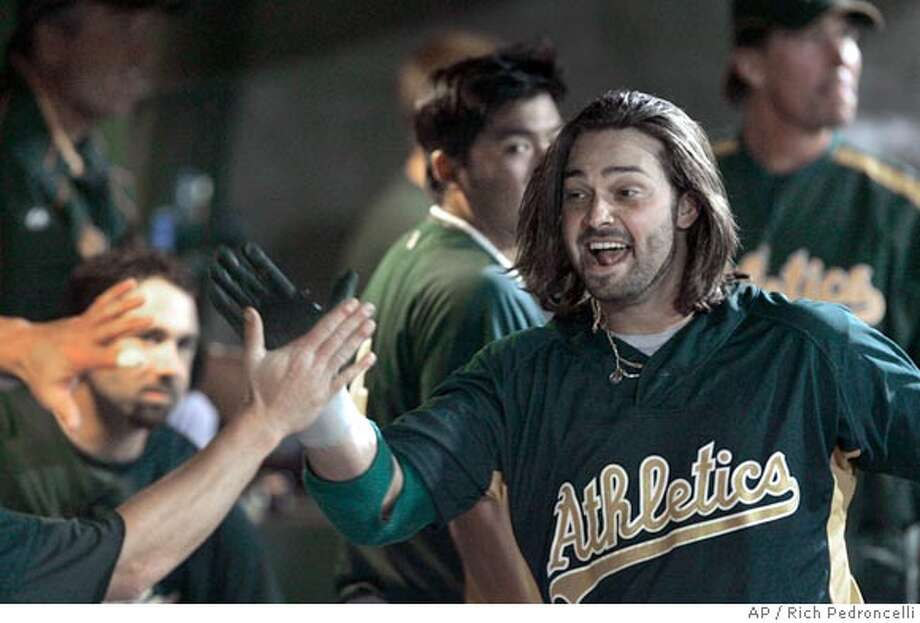 Oakland Athletics right fielder Nick Swisher right, slaps hands with teammates in the dugout after hitting his second home run in the top of the 9th inning against the Sacramento River Cats in an exhibition baseball game played between the A's and it's triple AAA affilate in West Sacramento, Calif., Thursday, March 29, 2007. The Athletics beat the River Cat's 11-10.(AP Photo/Rich Pedroncelli) Photo: Rich Pedroncelli