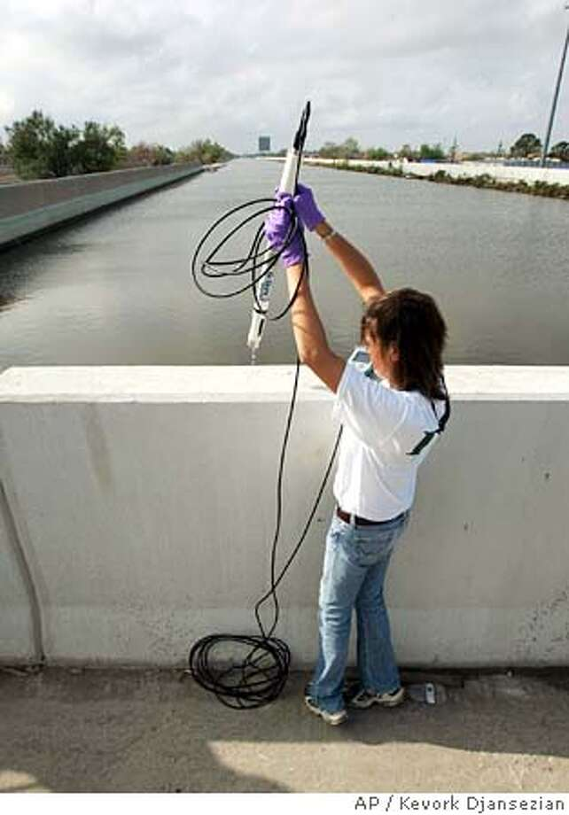 Kerry Michael-Jones, from Louisiana Department of Environmental Quality, lowers a device to test the quality of the water at the 17th Street Canal levee in New Orleans Thursday, Sept. 22, 2005. In the aftermath of Hurricane Katrina, New Orleans is keeping an eye on Hurricane Rita. (AP Photo/Kevork Djansezian) Photo: KEVORK DJANSEZIAN