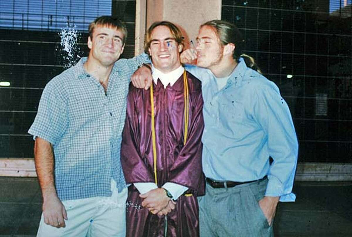 THIS IS A COPY PHOTO: It must have ink on it. Pat Tillman's graduation from Arizona State university, with brothers Kevin and Rich. Profile of Mary Tillman, mother of Pat Tillman (the football star who was killed by friendly fire in Afghanistan). This is for an A1 centerpiece story about Pentagon coverup of the case. She has big binders of the Pentagon files in the case that she has pored over, and a good portrait might be to have her spread them over her kitchen table (this image is described in the article) Also please pick up other photos and documents that she will give you to bring back to the Chronicle Graphics Dept for illustration purposes.