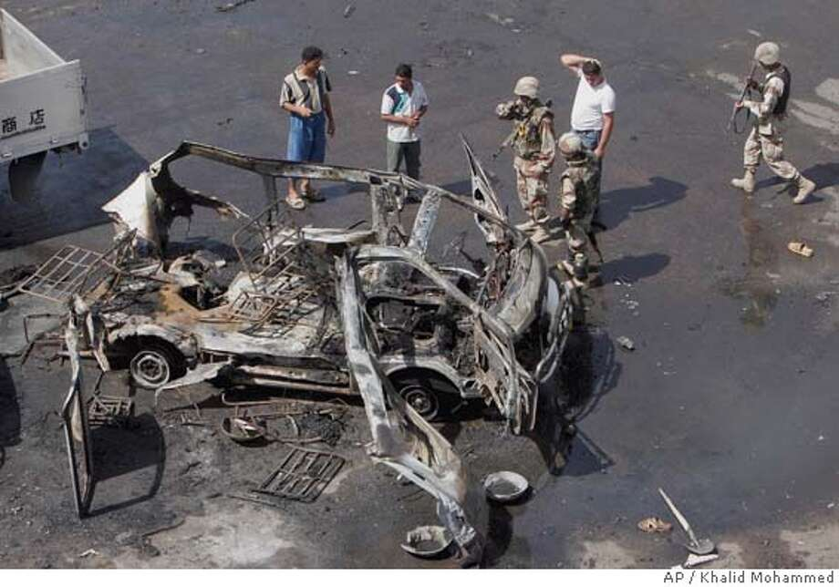 Iraqis stand around a minibus that was blown up by a suicide bomber in Baghdad, Iraq, Friday, Sept. 23 2005. A suicide bomber riding on the small public bus set off hidden explosives in a bustling open-air bus terminal Friday, the Muslim day of worship, killing at least five people and wounding eight, police said. (AP Photo/Khalid Mohammed) Ran on: 09-24-2005  Iraqis stand around a minibus that was blown up by a suicide bomber in central Baghdad. Photo: KHALID MOHAMMED