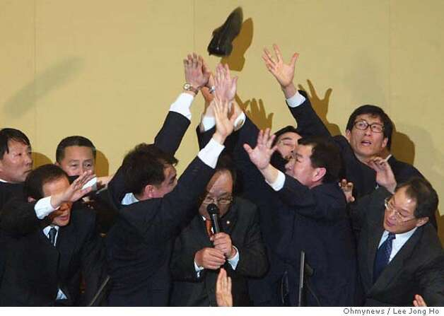 South Korean lawmakers and security personnel reach for a shoe thrown at Speaker Park Kwan Yong, center with microphone, during a scuffle in the National Assembly in Seoul Friday, March 12, 2004. Security guards at South Korea's parliament dispersed a sit-in to allow a vote to start on the impeachment or President Roh Moo Hyun, alleged to have broken election rules. Source: Lee Jong Ho/Ohmynews via Bloomberg News  Ran on: 03-28-2007  Oh Yeon Ho, publisher of OhmyNews, stands by his office in Seoul in this 2003 photo. The company plans an ambitious relaunch and seeks to double the number of citizen journalists in South Korea. Photo: LEE JONG HO