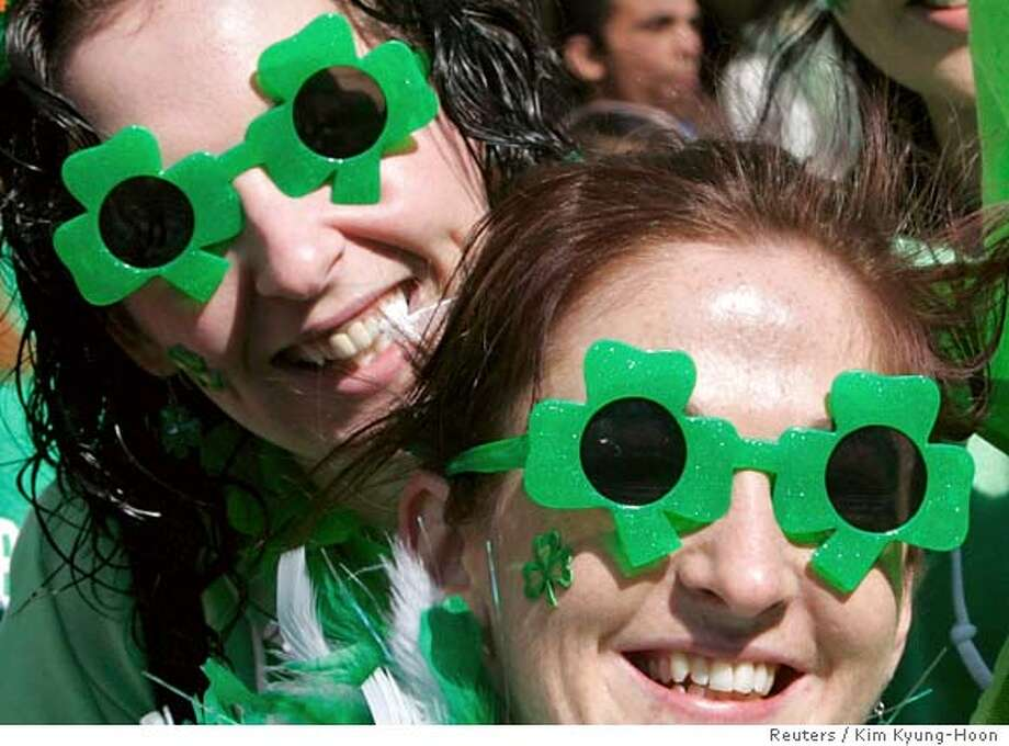 Irish women wear clover-shaped sunglasses as they watch a parade to celebrate Saint Patrick's Day in Tokyo March 18, 2007. REUTERS/Kim Kyung-Hoon (JAPAN) 0 Photo: KIM KYUNG-HOON