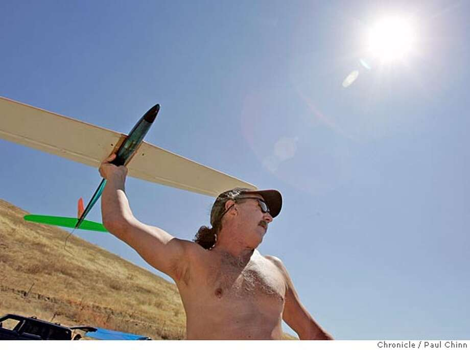 Steve Friday launches his glider into the wind. Model airplane enthusiasts fly radio-controlled gliders near Lake Del Valle on 9/3/05 in Livermore, Calif.  PAUL CHINN/The Chronicle Photo: PAUL CHINN
