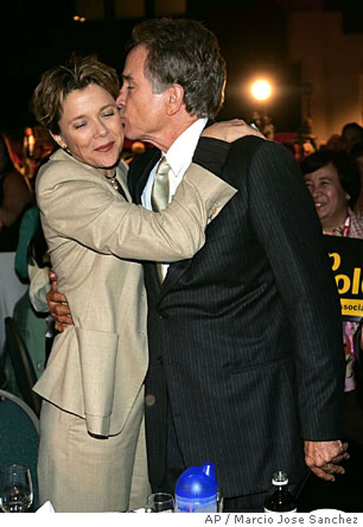 Actor Warren Beatty, right, kisses his wife actress Annette Benning after addresing members of the California Nurses Association on Thursday, Sept. 22 in Oakland, Calif. Beatty, a Democrat who has been mentioned as a possible challenger to Gov. Arnold Schwarzenegger next year, has in the past few months emerged as one of the governor's most visible and vociferous critics. (AP Photo/Marcio Jose Sanchez)